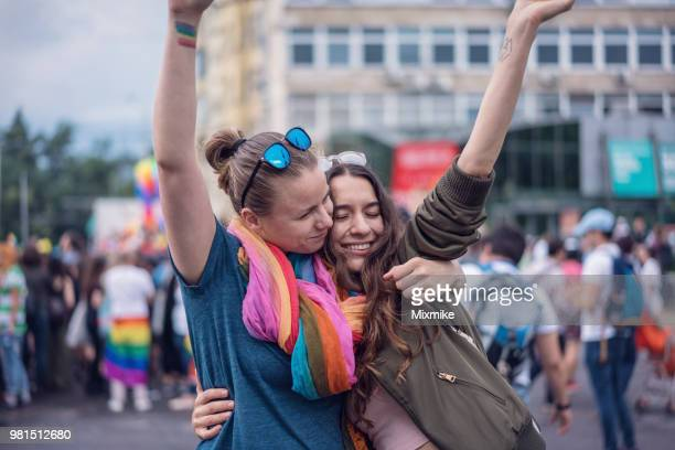 Beautiful female couple hugging while marching on the street