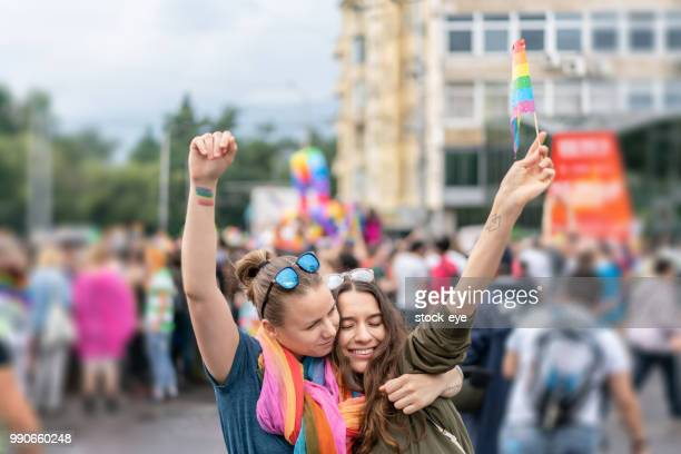 beautiful female couple hugging while marching on the street - demonstration stock pictures, royalty-free photos & images