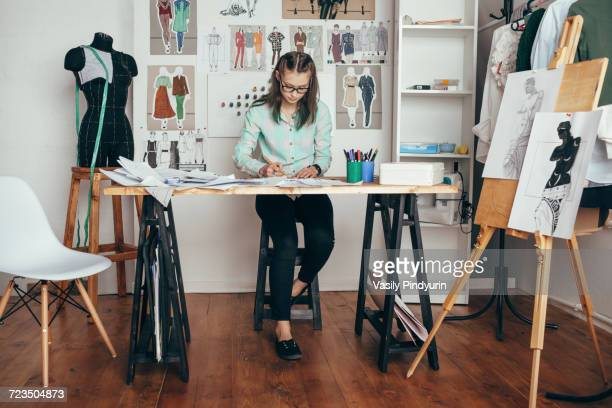 beautiful female design professional working at workbench in studio - fashion designer stock photos and pictures