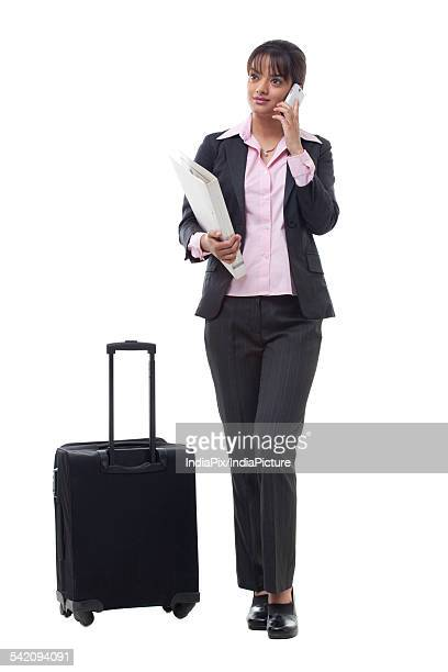 Beautiful female executive with luggage using mobile phone