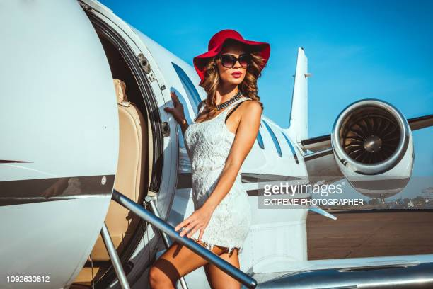 beautiful female fashion model entering a private jet parked on a taxiway - high society stock photos and pictures