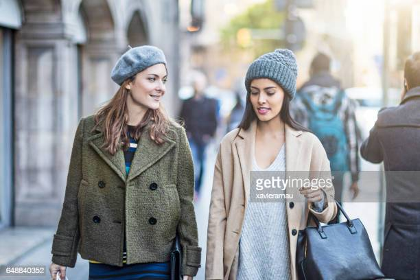 Beautiful female friends walking on sidewalk