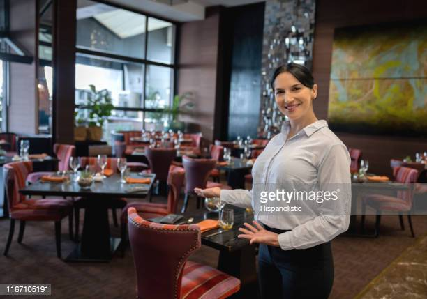 beautiful female hostess at a luxury hotel welcoming to restaurant while facing camera smiling - party host stock pictures, royalty-free photos & images