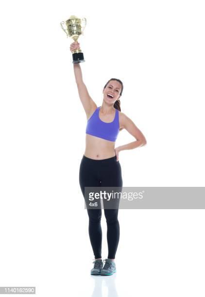 a fêmea bonita na roupa dos esportes está prendendo um troféu e é feliz - trophy - fotografias e filmes do acervo