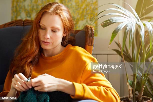 Hermosa mujer haciendo punto sentada en silla