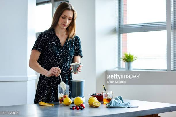 beautiful female making fresh fruit juice in her kitchen - milkshake imagens e fotografias de stock