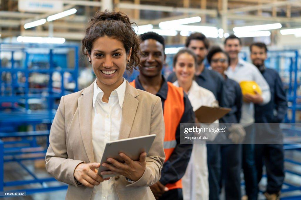 Schöne weibliche Managerin in einer Fabrik, die ein Tablet und ein Team von Arbeitern, Ingenieuren und Inspektoren hält, die in einer Reihe stehen und vor der Kamera lächeln : Stock-Foto