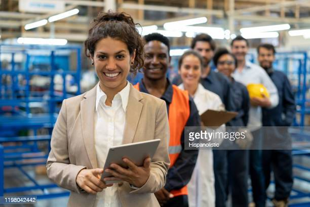 beautiful female manager at a factory holding a tablet and team of blue collar workers, engineers and inspectors standing in a row smiling at camera - occupation stock pictures, royalty-free photos & images