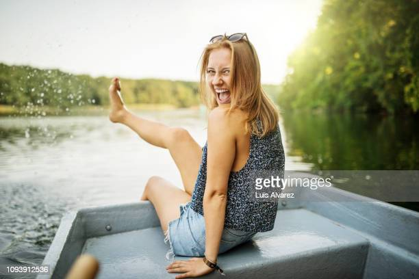beautiful female on boat ride in lake having fun - summer stock-fotos und bilder