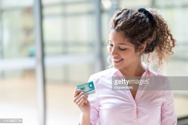 beautiful female patient at the hospital holding her insurance card smiling - hispanolistic stock photos and pictures