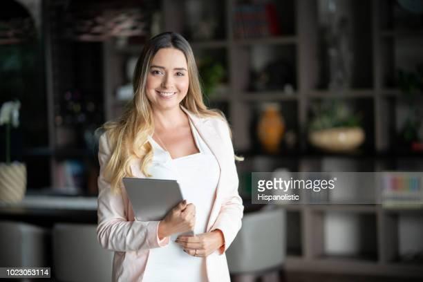 Belle femelle agent immobilier à une propriété tenant une tablette et regardant sourire caméra