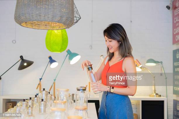 a beautiful female shopping in a lifestyle store - ギフトショップ ストックフォトと画像