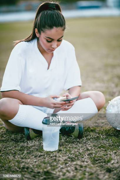 Beautiful Female Soccer Player Typing On Smartphone Before Match