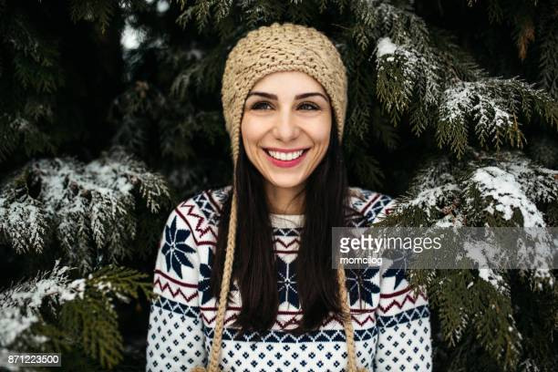 Beautiful female standing outdoor in front of snowy pine tree