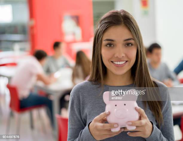 Beautiful female student at the library holding a piggy bank looking at camera smiling
