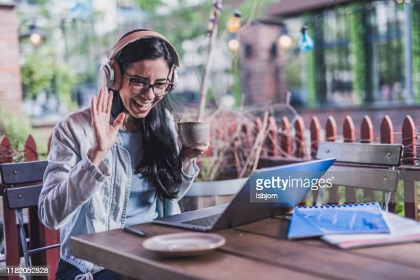 mooie vrouwelijke student drinken koffie en skyping in cafetaria. - koffiepauze stockfoto's en -beelden