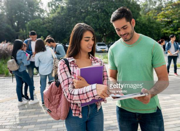 beautiful female student pointing something at her friends notebook while smiling at the college campus - hispanolistic stock photos and pictures
