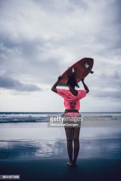 beautiful female surfer with surfboard at tropical beach at sunset - thong bikini stock pictures, royalty-free photos & images