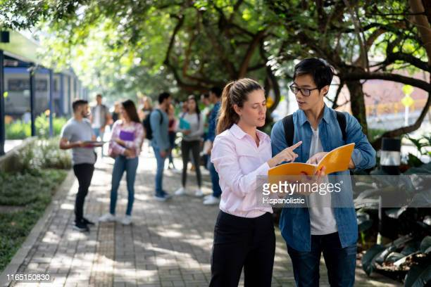 beautiful female teacher answering a question for an exchange student pointing at his notebook while standing around the college campus - hispanolistic stock photos and pictures