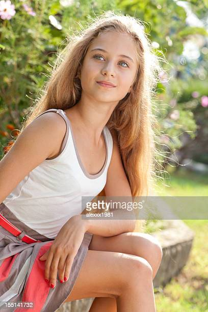 Beautiful female teenager sitting outdoors on curbs, posing, looking away