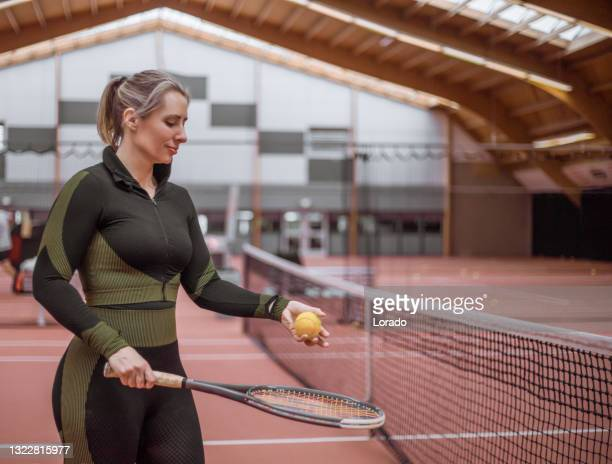 a beautiful female tennis player on the indoor court - international match stock pictures, royalty-free photos & images