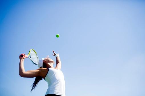Beautiful female tennis player serving 483794130