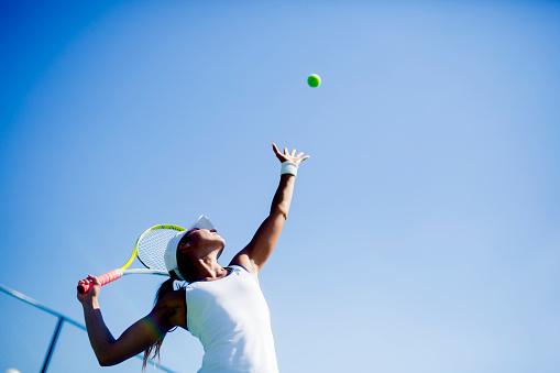 Beautiful female tennis player serving 517090082