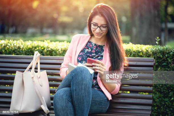 Beautiful female texting on her phone in the park