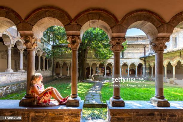 beautiful female tourist sitting at the interior of cloister of piona abbey wearing floreal dress. piona abbey, colico, lake como, lecco province, lombardy, italy. - italia stockfoto's en -beelden
