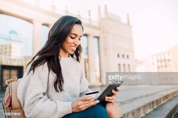 beautiful female tourist using tablet for online shopping technology - questão da mulher imagens e fotografias de stock
