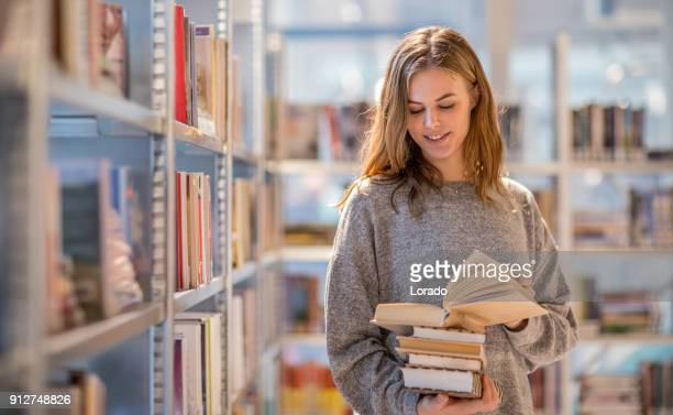 Beautiful female university student studying on campus library