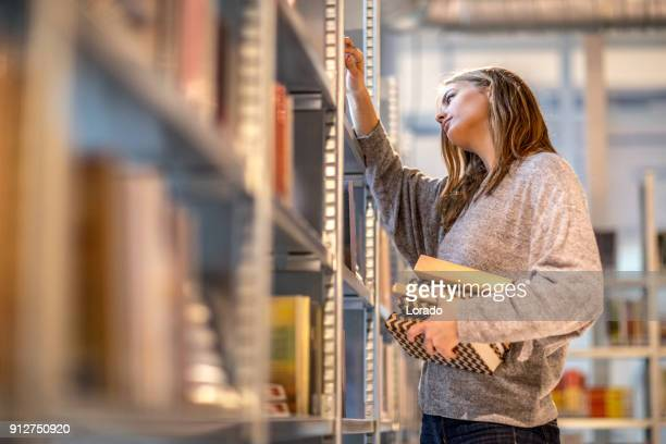 beautiful female university student studying on campus library - linguistics stock pictures, royalty-free photos & images