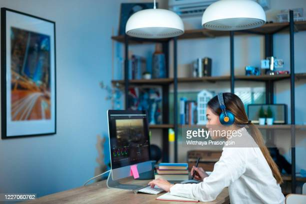 beautiful female video editor works with footage on her personal computer, she works in creative office studio - multimedia stock pictures, royalty-free photos & images