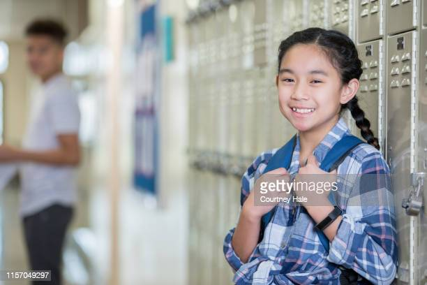beautiful filipino girl is student in public junior high school, and is leaning against lockers - charter_school stock pictures, royalty-free photos & images