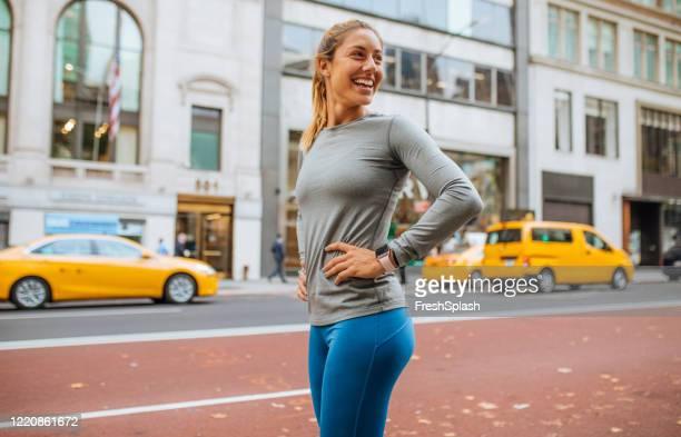 mooie fit blonde vrouw op de straten van nyc tijdens haar morning run - lange mouwen stockfoto's en -beelden
