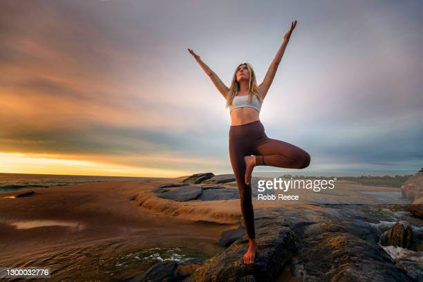 beautiful, fit woman practicing yoga on rocky beach - robb reece stock pictures, royalty-free photos & images
