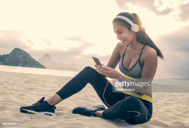 beautiful fit woman using her smartphone after workout
