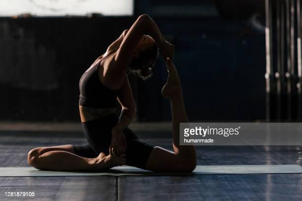 belle jeune femme en forme et sa routine quotidienne de yoga - gymnastique au sol photos et images de collection