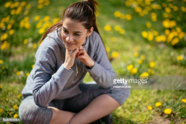 beautiful fitness girl sitting on a grass - sweatshirt stock pictures, royalty-free photos & images