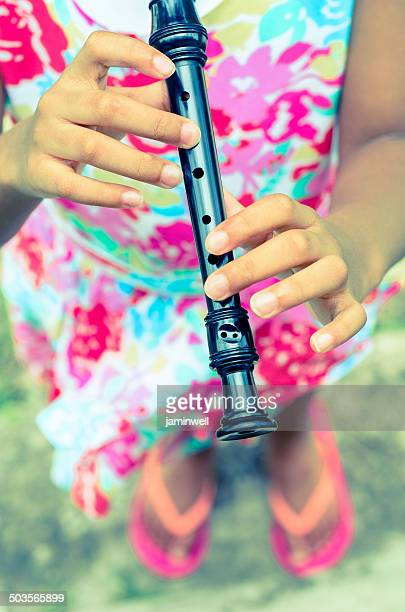 beautiful floral dress and flute playing girl - recorder musical instrument stock photos and pictures