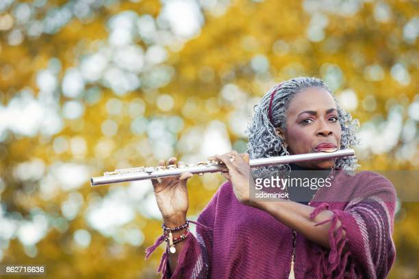 Beautiful Flute Player With Fall Trees Behind Her