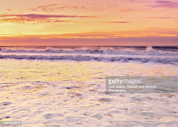 beautiful foamy water and pink sunrise sky at jones beach, long island - wantagh stock pictures, royalty-free photos & images
