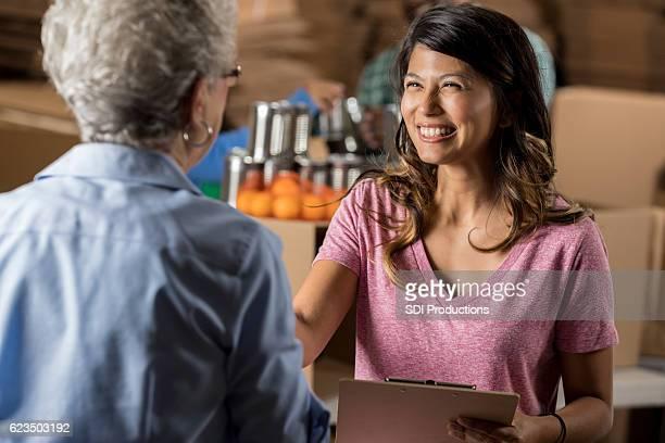 Beautiful food bank organizer greets senior volunteer