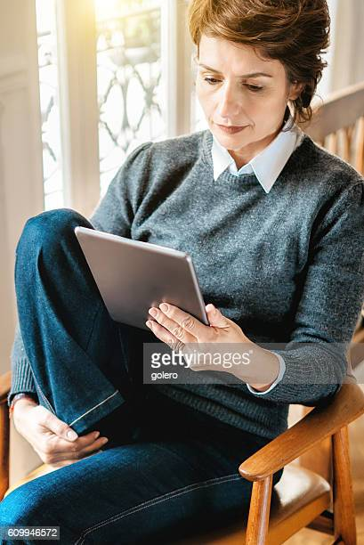 beautiful  french woman reading on tablet in Paris apartment