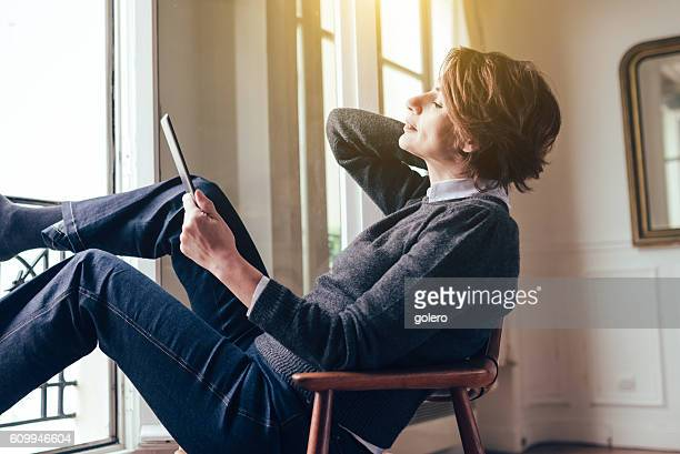 beautiful  french woman relaxing with tablet in paris apartment - french women stock-fotos und bilder