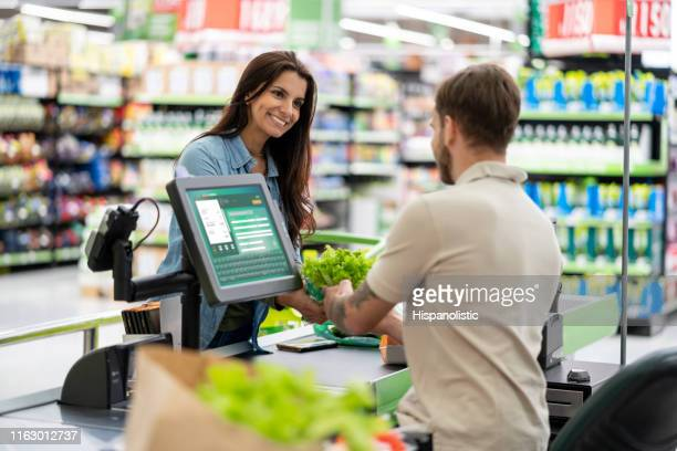 beautiful friendly customer at checkout smiling at male cashier while he scans products in a supermarket - cash register stock pictures, royalty-free photos & images
