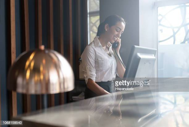 beautiful friendly hotel receptionist answering a call from a guest - making a reservation stock photos and pictures