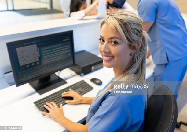 beautiful friendly nurse at the front desk of the hospital working on computer while facing camera smiling - medical receptionist uniforms stock pictures, royalty-free photos & images