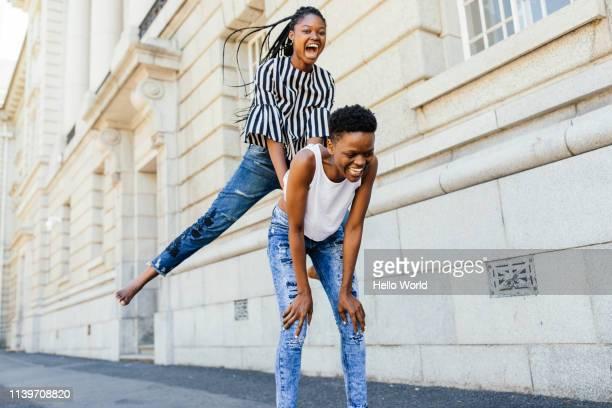 Beautiful gappy friends playing leapfrog barefoot on the pavement