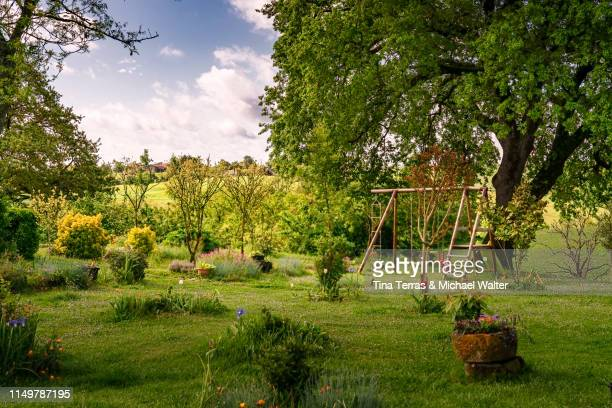 beautiful garden with flowers, lawn and children's toys in france. - jardín formal fotografías e imágenes de stock